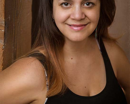 headshot of Ariel looking into the camera, hair dark brown long and straightened, wearing a black tank