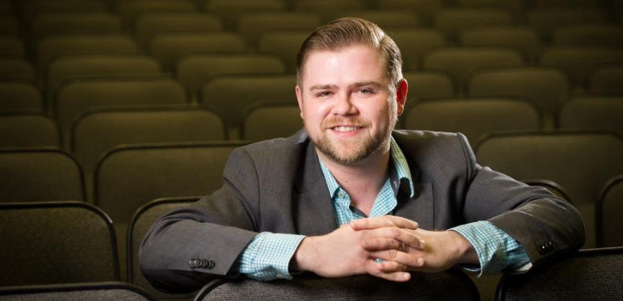 David wears a short beard, gray suitcoat with teal checked shirt, and is leaning over the back of seat in an empty theatre