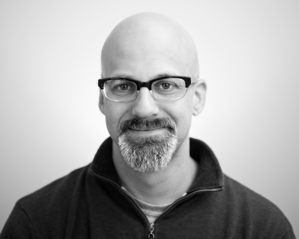 a lack and white headshot of Thaddeus. He wears dark rimmed glasses, a salt and pepper goatee, and a bald head with a dark collared collared zip up.